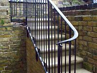 Bespoke handrail for the basement of a terraced house, viewed from the foot of the stairs.
