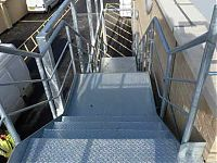 steel staircase with hand rail and security mesh.