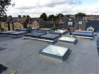 Solar heaters mounted on aluminum brackets, situated on top of a roof in a residential area of oxford.
