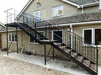 a bespoke fabricated steel staircase two stories high with a bride to the door