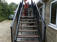 A bespoke first floor steel staircase. view from the bottom of the stair with employee stood on the stairs
