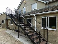 A bespoke first floor steel staircase, with a bridge platform to the door. view from the ground floor.